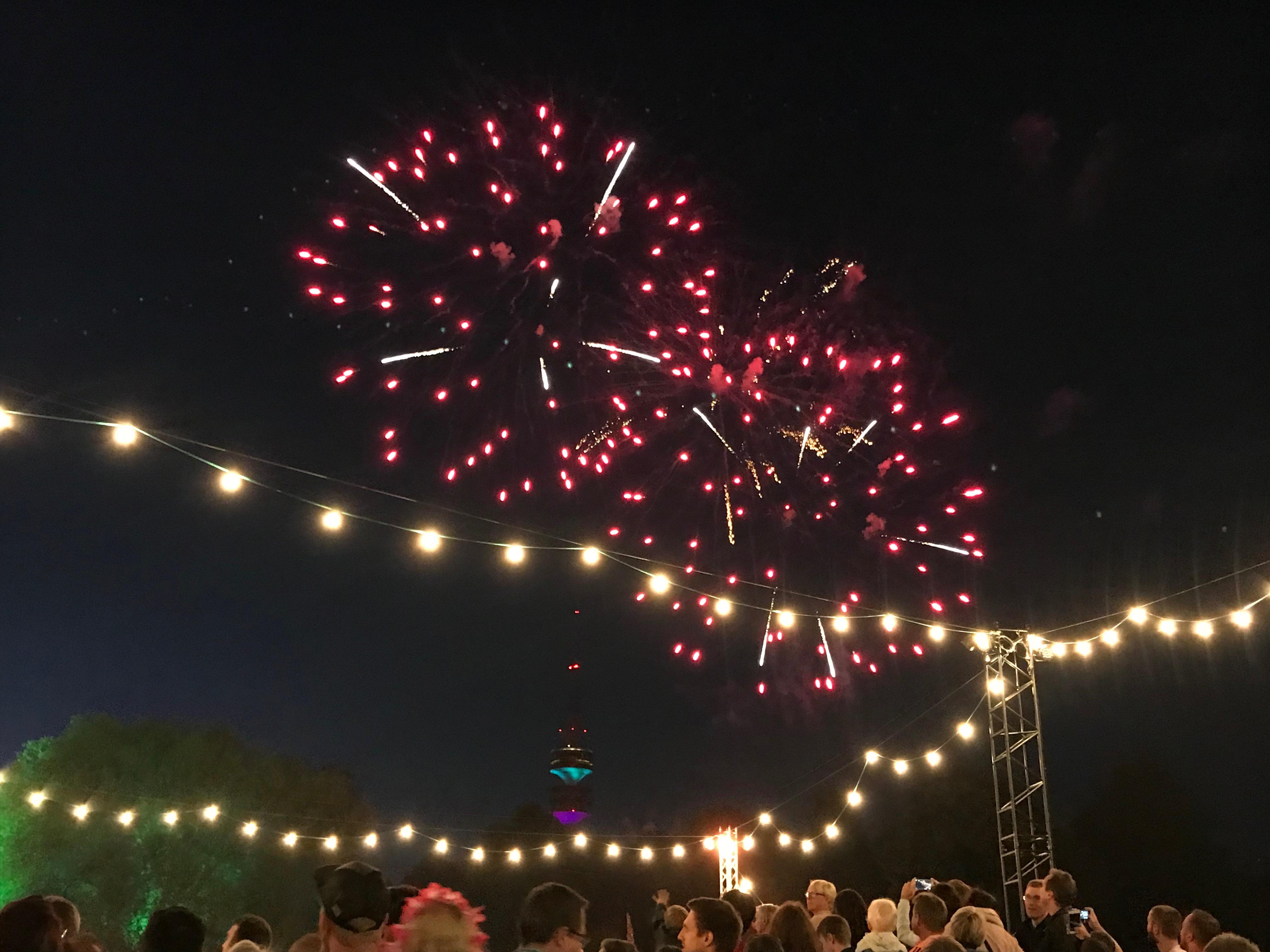 Rotes Feuerwerk über dem Tollwood Festival und im Hintergrund der Olympiaturm